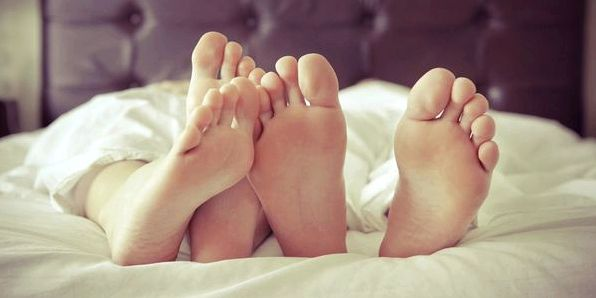 Couple feet in bed sheets' /
